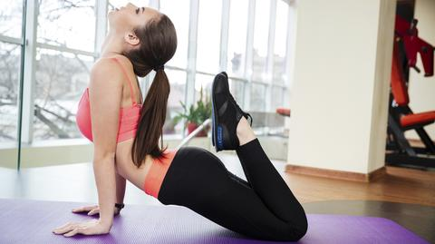 Beautiful young sportswoman relaxing and stretching on yoga mat in gym
